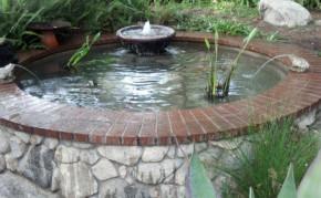 Pond construction: round brick and rock pond