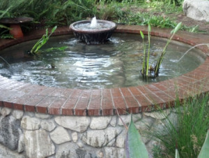 Pond construction: round brick and rock pond